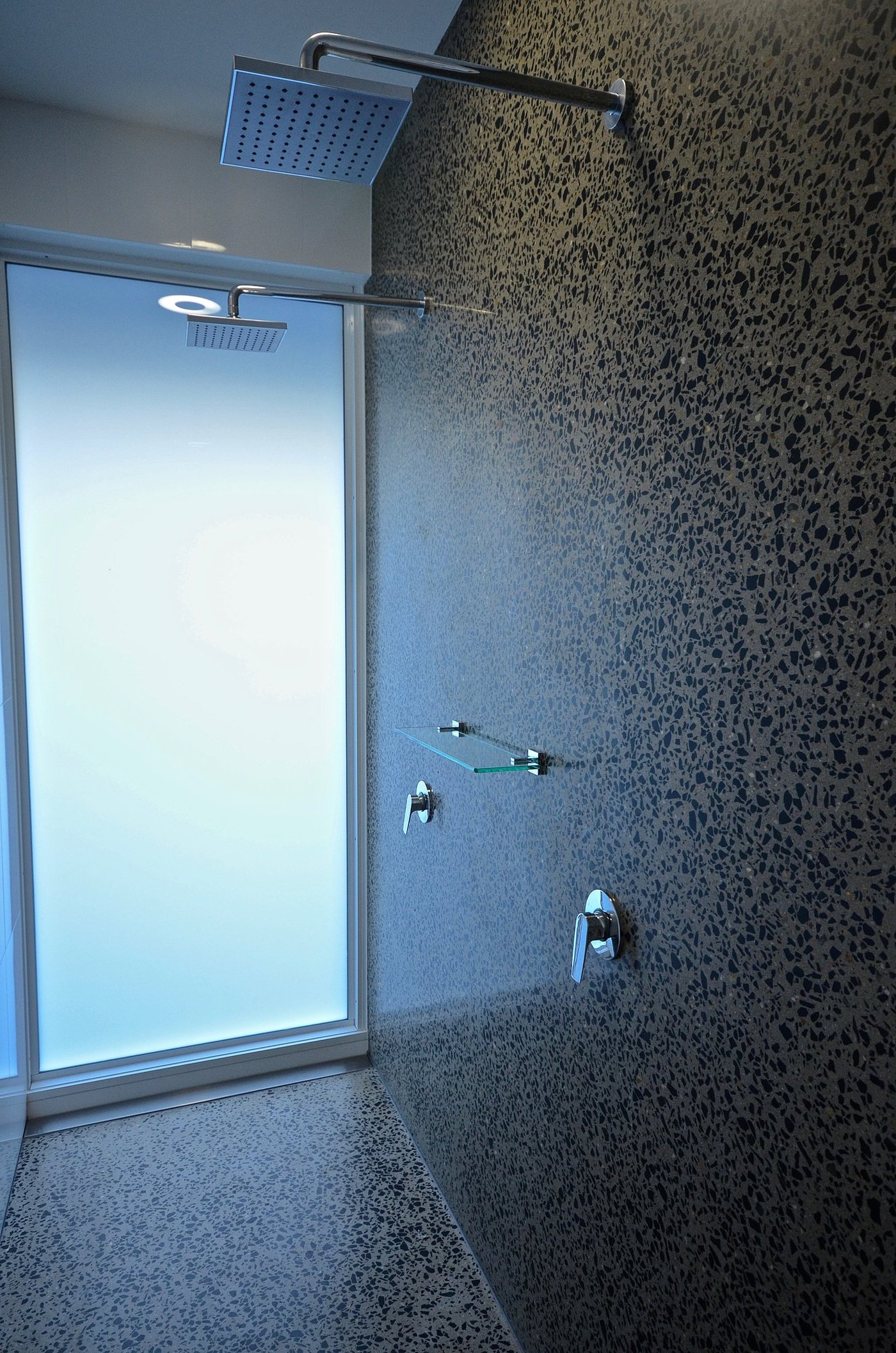 Twin showers with honed concrete floor and walls
