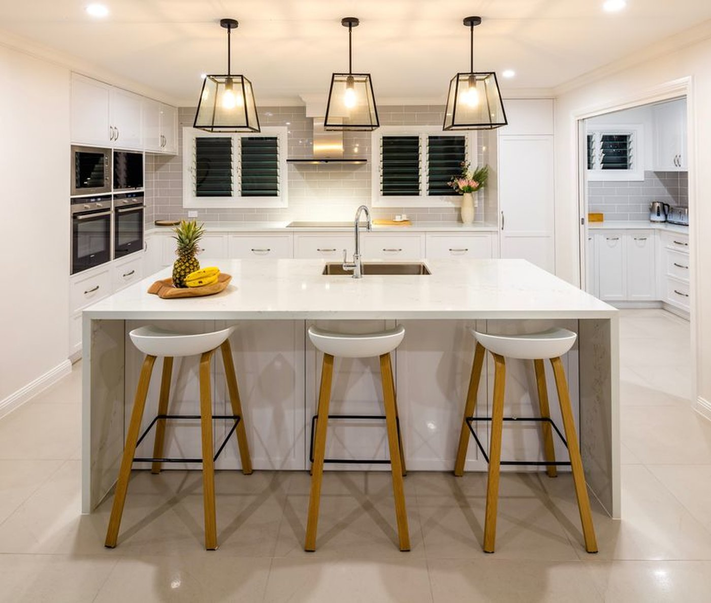 New white kitchen with island bench, three stools and three hanging pendant lights