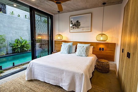 Bedroom with handmade headboard, hanging pendant lights and pool access