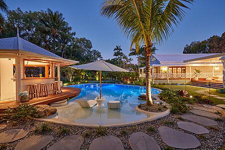 Night Photo of Resort Style Pool with cabana, landscaping, lighting & audio