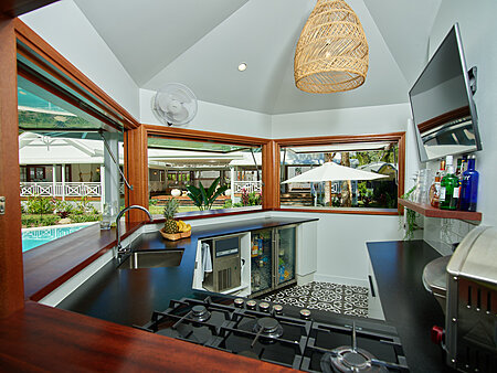 Custom designed pool cabana kitchen with tv and fan overlooking pool