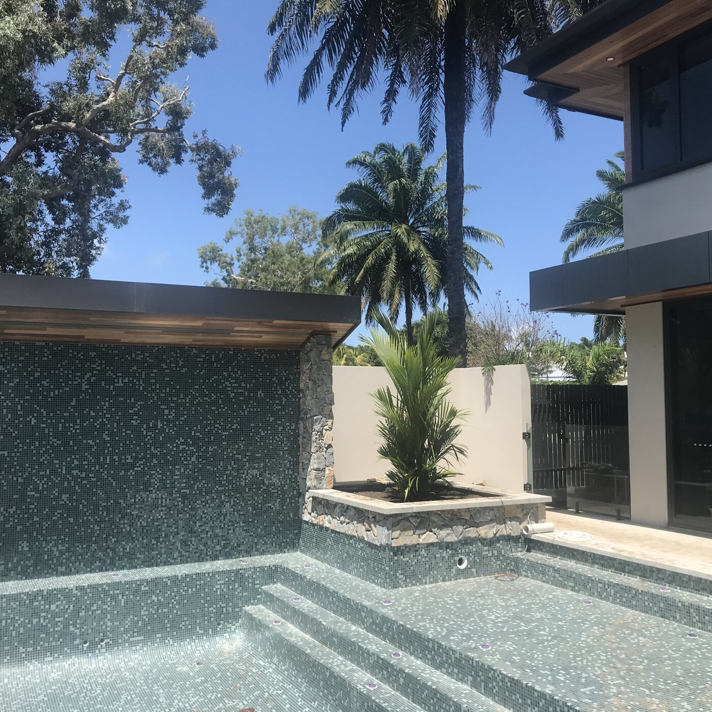 Tiled pool with water feature construction underway